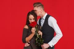 Парень обнимает и целует девушку в голове которая пахнет букетом роз в ее руках на красной предпосылке Стоковые Изображения RF