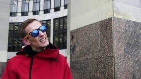 Парень портрета тонкий в красной куртке и солнечных очках ударяя рядом со столбцами гранита видеоматериал