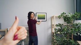 Парень порции женщины для выбора места для изображения в комнате показывая жестами и говоря сток-видео