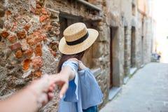 Парень после подруги держа руки в старой европейской улице смеясь над и усмехаясь Стоковая Фотография RF