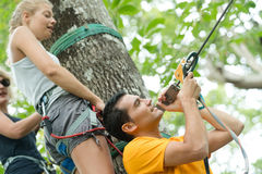 Парень подготавливая веревочку для подруги в парке приключения Стоковая Фотография