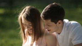 Парень при девушка сидя в парке и смотря таблетку Конец-вверх акции видеоматериалы