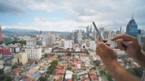 Парень работает со смартфоном на запачканной предпосылке Куала Лумпур Руки и поднимающее вверх телефона близкое Малайзия видеоматериал
