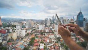 Парень работает со смартфоном на запачканной предпосылке Куала Лумпур Руки и поднимающее вверх телефона близкое Малайзия акции видеоматериалы