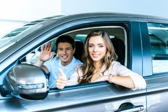 Парень развевая рука, подруга показывая большой палец руки вверх сидя в новом автомобиле в выставочном зале стоковое фото