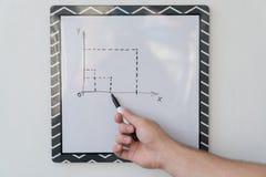 Парень рисует план-график на белой доске Мужская рука с отметкой на предпосылке белой доски Стоковая Фотография