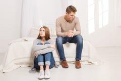 Парень сидит на кровати, и девушка на поле не говорит друг к другу indoors Стоковое фото RF