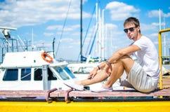 Парень сидит на пристани Стоковое Фото