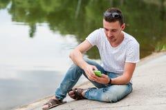 Парень смотрит телефон Сидеть озером Стоковая Фотография RF