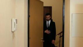 Парень с бородой в костюме и связи говорит стоять в двери квартиры, тогда закрывает дверь снаружи 4K r видеоматериал