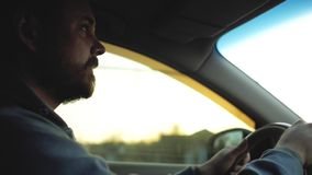 Парень с бородой и усиком управляет автомобилем на заходе солнца сток-видео