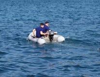 Парень с девушкой в красном раздувном rowing шлюпки на море Середины спасения от оборудования круиза плавать тускло Остатки на th Стоковые Изображения RF