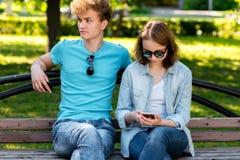 Парень с девушкой в лете в парке в природе Они сидят на стенде В руках smartphone читает social Стоковые Фото