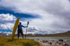 Парень с каяком на береге озера высокой горы kyrgyzstan Стоковая Фотография RF