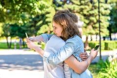 Парень с объятиями девушки Лето в природе В руках держать smartphones Соответствовать в социальных сетях _ стоковое фото