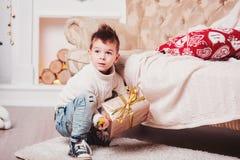 Парень с стильной iroquois стрижкой и в модных современных одеждах сидит рядом с софой и доволен с подарком Милое Стоковое Фото
