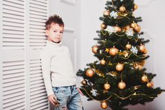 Парень с стильной iroquois стрижкой и в модных современных одеждах стоит около белой стены рядом с рождественской елкой A.C. Стоковое фото RF