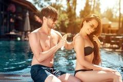 Парень трет заднюю часть ` s девушки с солнцезащитным кремом около бассейна стоковое фото