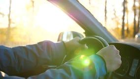 Парень управляет автомобилем на солнечный день Время захода солнца Крупный план рук и рулевого колеса сток-видео