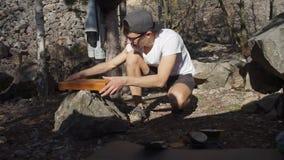 Парень устанавливает таблицу на камне сток-видео