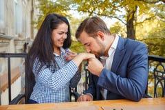 Парень целует руку ` s девушки снаружи Стоковое Изображение