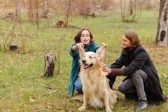 Парень штрихует собаку и девушка подняла ее уши в древесинах для прогулки Стоковое фото RF