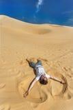 Парень Appy кладя на песок и делая ангела песка Стоковая Фотография