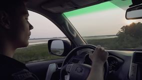 Парень Attraktive управляет большим автомобилем против фона красивого мужчины захода солнца путешествует на сельской местности акции видеоматериалы
