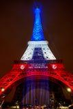 ПАРИЖ - 16-ОЕ НОЯБРЯ: Эйфелева башня загоренная с цветами французского национального флага в день оплакивать 16-ого ноября 2015 Стоковое Фото