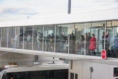 Париж, Франция - апрель 2016: Люди всходя на борт airplain используя прозрачный мост двигателя Взгляд со стороны от терминала стоковое фото rf