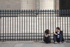 Париж, Франция - 12-ое апреля 2011: молодая женщина и человек сидя совместно около загородки стоковые фото