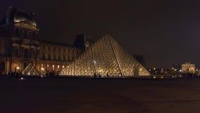 ПАРИЖ, ФРАНЦИЯ - 31-ОЕ ДЕКАБРЯ 2016 Steadicam сняло силуэтов туристов около стеклянной пирамиды жалюзи на ноче известно сток-видео