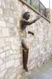 Париж, Франция, 26-ое марта 2017: Человек который шел через Стену, 1989 ` Le Passe-Muraille ` скульптуры Джина Marais дальше Стоковое Фото