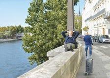 ПАРИЖ, ФРАНЦИЯ - 16-ОЕ ОКТЯБРЯ 2016: Человек сидит и отдыхает на малой стене около реки Sena Стоковые Изображения