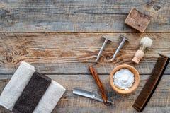 парикмахерскаь ` Брить и стрижка s людей Щетка, бритва, пена на copyspace взгляд сверху предпосылки деревянного стола стоковая фотография