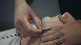 Парикмахер бреет бороду клиента в парикмахерскае видеоматериал