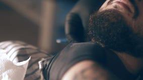 Парикмахер бреет его голову, усик и бороду к человеку в парикмахерскае Стилизатор использует классическую острую бритву сток-видео