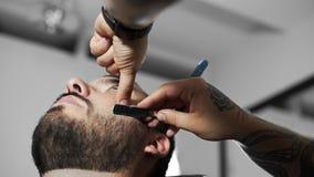 Парикмахер бреет клиента с прямым лезвием бритвы, стрижкой ` s человека и брить на парикмахере, парикмахерской и брить акции видеоматериалы