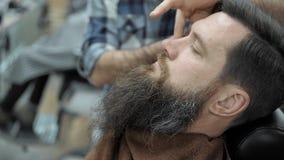 Парикмахер бреет людей с длинной бородой с прямым лезвием бритвы в парикмахерской или парикмахерскае s Стрижка и брить ` s челове акции видеоматериалы