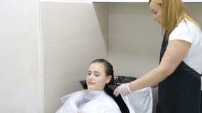Парикмахер в перчатках моя волосы ` s молодой женщины в салоне сток-видео