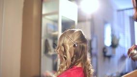 Парикмахер в салоне красоты делает стиль причёсок для белокурой девушки акции видеоматериалы