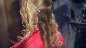 Парикмахер в салоне красоты делает стиль причёсок для белокурой девушки сток-видео