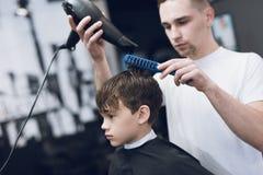 Парикмахер делает модный милый стиль причёсок для мальчика в современной парикмахерскае Стоковое Фото