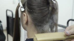 Парикмахер делает слоение волос в салоне красоты для девушки с волосами брюнета сток-видео