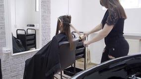 Парикмахер делает слоение волос в салоне красоты для девушки с волосами брюнета акции видеоматериалы