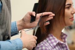 Парикмахер делая стильную стрижку с профессиональными ножницами стоковое фото