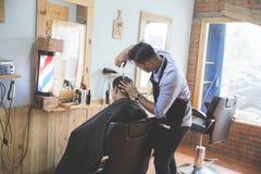 Парикмахер делая стрижку привлекательного человека в парикмахерскае Стоковые Изображения RF