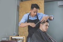 Парикмахер делая стрижку привлекательного человека в парикмахерскае Стоковая Фотография