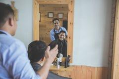 Парикмахер делая стрижку привлекательного человека в парикмахерскае Стоковое Фото