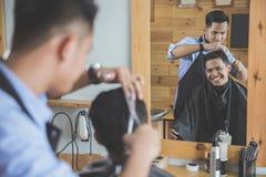 Парикмахер делая стрижку привлекательного человека в парикмахерскае Стоковое фото RF